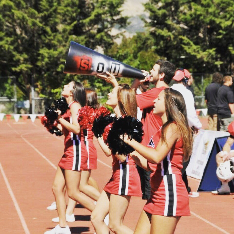 """A group of femme cheerleaders in red  and black traditional cheerleading uniforms with red and black pom poms and a masculine cheerleader with a big black megaphone that has the letters """"SOU"""" spray painted on it, are lined up on a running track performing a cheer."""